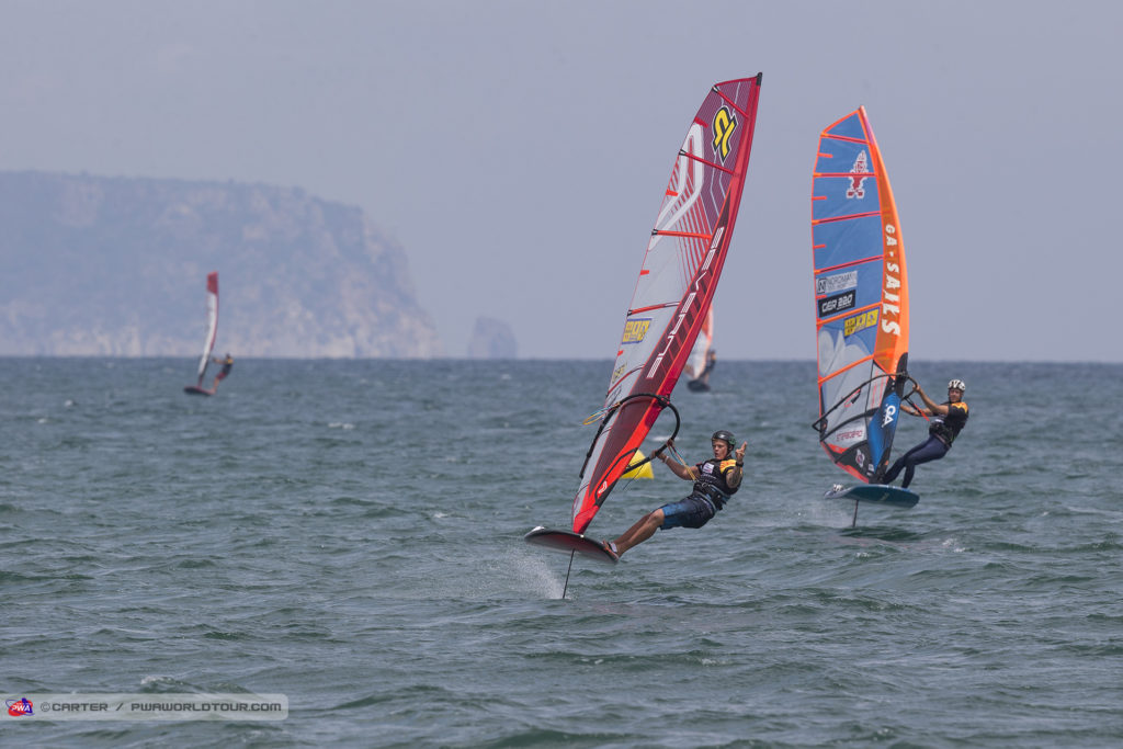 The 2018 Catalunya PWA World Cup began with a glorious sunny morning as the sailors rigged and registered for the next 6 days of competition. A golden start to the day During the early afternoon, the wind kicked in, but fluctuated greatly in strength and direction throughout - mainly between 5-17 knots - which made racing tricky at times, but even so the first two foil eliminations were completed. However, a thundery squall soon brought proceedings to an end shortly after 5pm as the unsettled weather continues. Amado Vrieswijk emerges Foiling In South Korea, there were 4 separate winners from the 4 eliminations completed and that trend continued today as each race was claimed by a different sailor - Amado Vrieswijk (JP / Severne) and Julien Bontemps (JP / NeilPryde). Before today Amado Vrieswijk (JP / Severne) had won foil eliminations in both New Caledonia and South Korea - where he missed out on the podium by just 0.7 of a point - but after the opening day here the Bonairean can add another location to his bullet collection as the hugely, multi-talented 22-year-old continues to establish himself in the racing world. Vrieswijk, who has finished the last two seasons as the vice-world champion in freestyle, made a perfect start, as he claimed the opening bullet of the week ahead of Sebastian Kördel (Starboard / GA Sails) after overtaking the German around the final mark. And then cemented his place at the top of the overnight rankings with an excellent second place in race two as he chases a first podium in racing. Amado Vrieswijk shoots for the No.1 spot